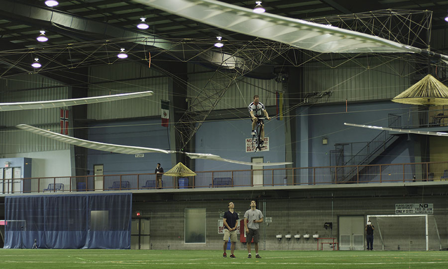 Pilot pedals helicopter above the ground crew at indoor soccer field.