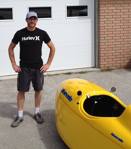Randy standing in front of a Yellow velomobile